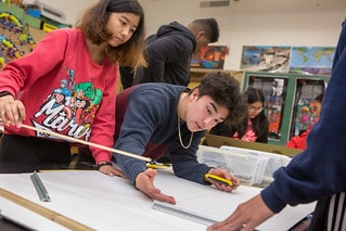 Students in Skyline High School's Green Energy Pathway cut cardboard to make the frame for a solar house model.  PHOTO CREDIT: Courtesy of Allison Shelley/The Verbatim Agency for American Education: Images of Teachers and Students in Action