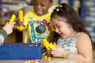 Preschool students practice hammering and removing plastic nails from a foam pad in a sensory center.  Photo by Allison Shelley/The Verbatim Agency for American Education: Images of Teachers and Students in Action
